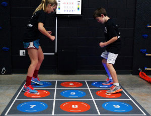 Kids playing on Pavigym Square - an interactive flooring product.